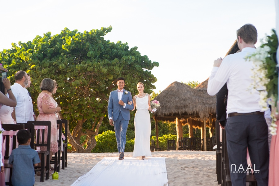 Bride and groom walking to the aisle at Blue Venado beach Club by Naal Wedding Photography